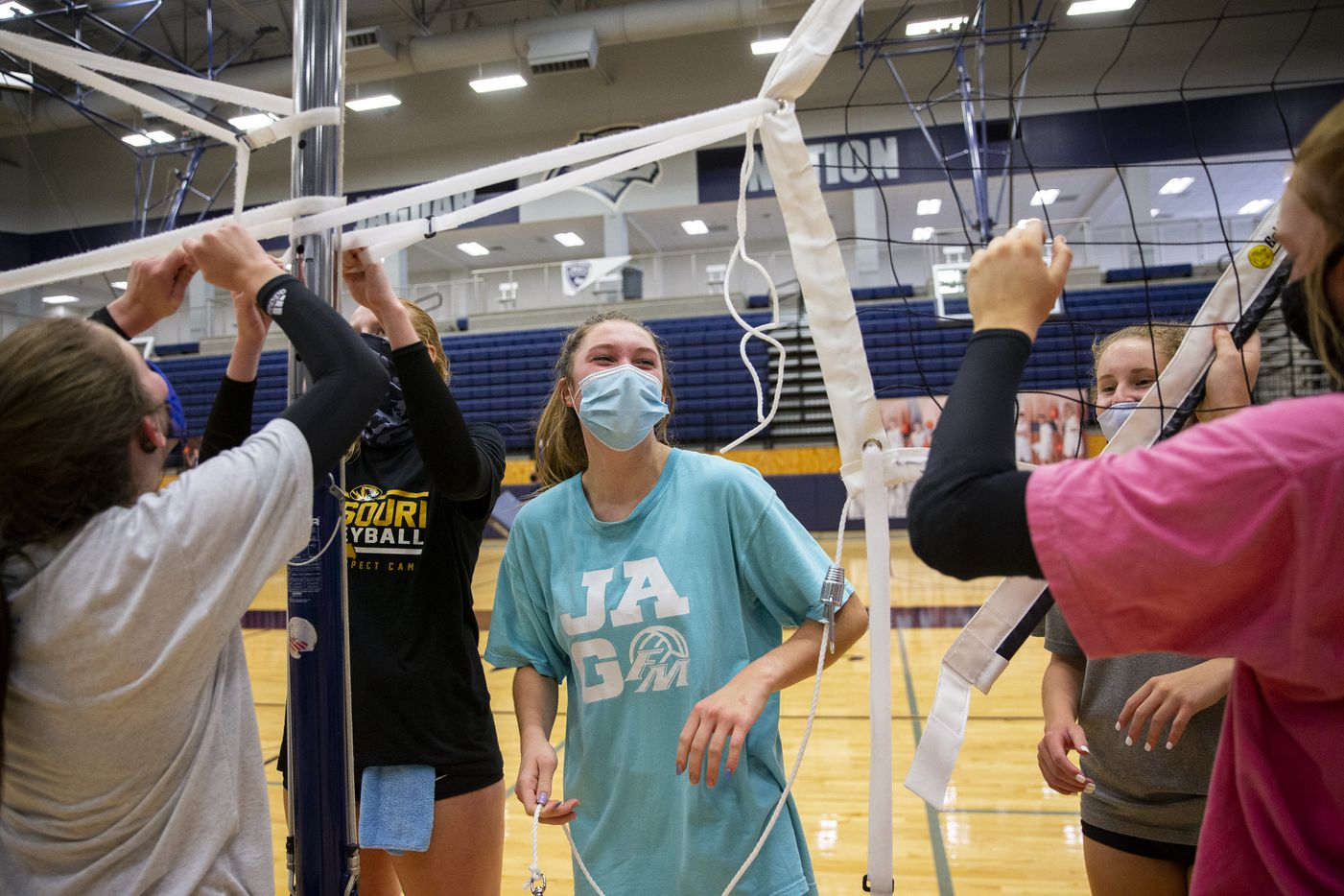 Flower Mound High School volleyball player Caroline Dykes (center) laughs with teammates as they put up the nets after practice on Sept. 8, 2020 in Flower Mound. (Juan Figueroa/ The Dallas Morning News)