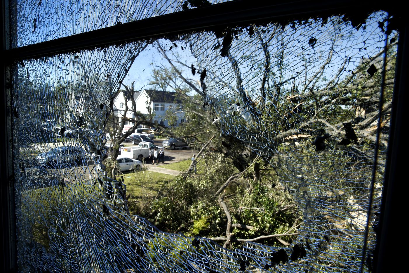 Damaged homes and down trees on Pemberton Drive in Dallas are seen through Eva wiley's shattered window, Monday, October 21, 2019. A tornado tore through the neighborhood knocking down trees and ripping roofs from homes.