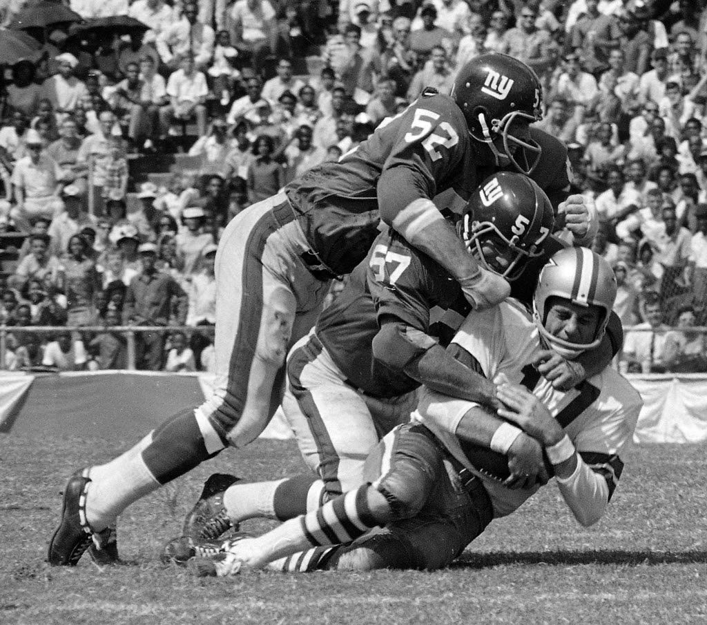 Dallas Cowboy quarterback Don Meredith (17) is tackled after an 8-yard run in the second quarter of a game at the Cotton Bowl against the New York Giants on Sept. 24, 1967, two days after the birth of his only son. (AP Photo)
