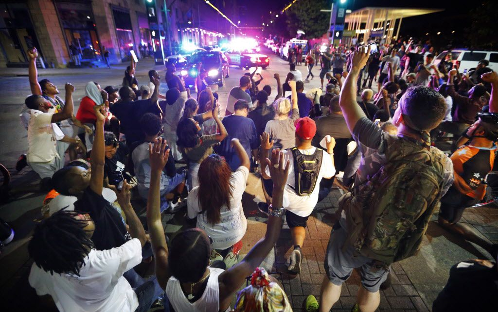 Like San Francisco quarterback Colin Kaepernick, protesters take a knee in the intersection of Main St. and S. St. Paul forcing the police to move in with riot gear during the Next Generation Action Network protest in downtown Dallas, Thursday, September 22, 2016. In response to the police killings, the group is standing in solidarity with the families and all of those who want justice for all.