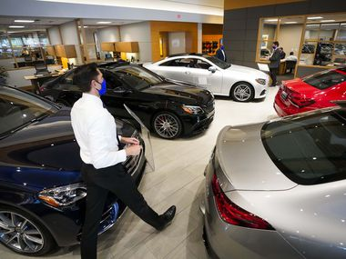 Sales Consultant Erik Bohdan walks through the showroom at Park Place Motorcars Dallas on Tuesday, April 21, 2020, in Dallas.