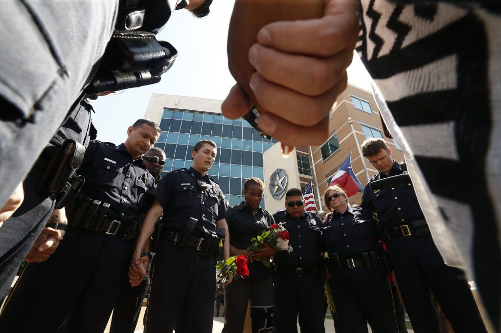 Dallas Police pray in front of Jack Evans Police Headquarters in Dallas on Friday July 8, 2016 after a deadly shooting in downtown Dallas where 5 police officers were killed on the night before. (Nathan Hunsinger/The Dallas Morning News)