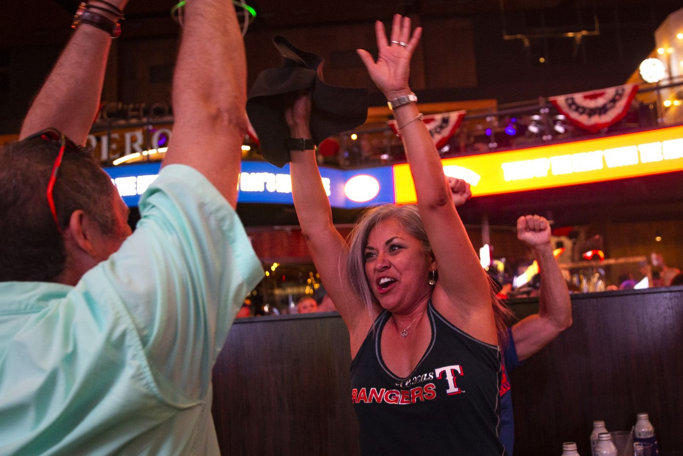 Claudia Borunda (right), from California, cheers with fans as the Texas Rangers win their opening day game of their season at Texas Live! in Arlington, Texas, on Friday, July 24, 2020. The Rangers played the Colorado Rockies at the new Globe Life Field stadium, but fans had to watch on televised screens outside due to the ongoing pandemic. (Lynda M. Gonzalez/The Dallas Morning News)