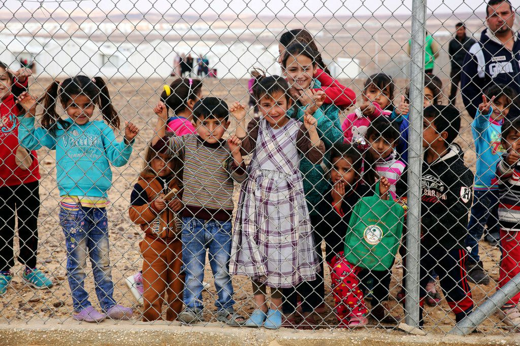 Syrian refugee children gather behind a fenced-off area of the Azraq camp for Syrian refugees in Azraq, Jordan.