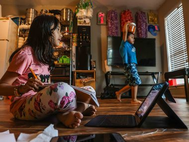 Zakirah Binti Mohammad Yasin, 7, attends a tutoring session by McShan Elementary School from her home via Zoom as her brother Uzaifah Bin Yasin, 3, walks around the living room. The program helps a largely immigrant student population learn to read in English.