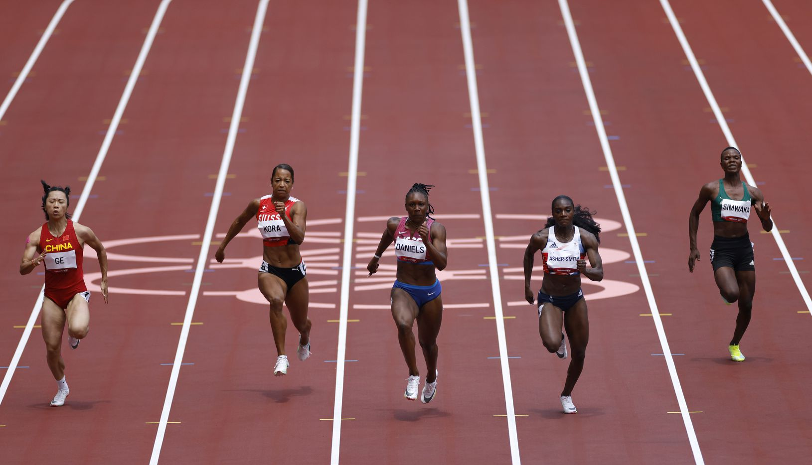 USA's Teahna Daniels (lane 5) competes in the  women's  100 meter race during the postponed 2020 Tokyo Olympics at Olympic Stadium, on Friday, July 30, 2021, in Tokyo, Japan. Daniels finished with a time of 11.04 seconds to advance to the next round. China's Manqi Ge, Switzerland's Salome Kora, Great Britain's Dina Asher-Smith, and Malawi's Asimenye Siwaka compete. (Vernon Bryant/The Dallas Morning News)