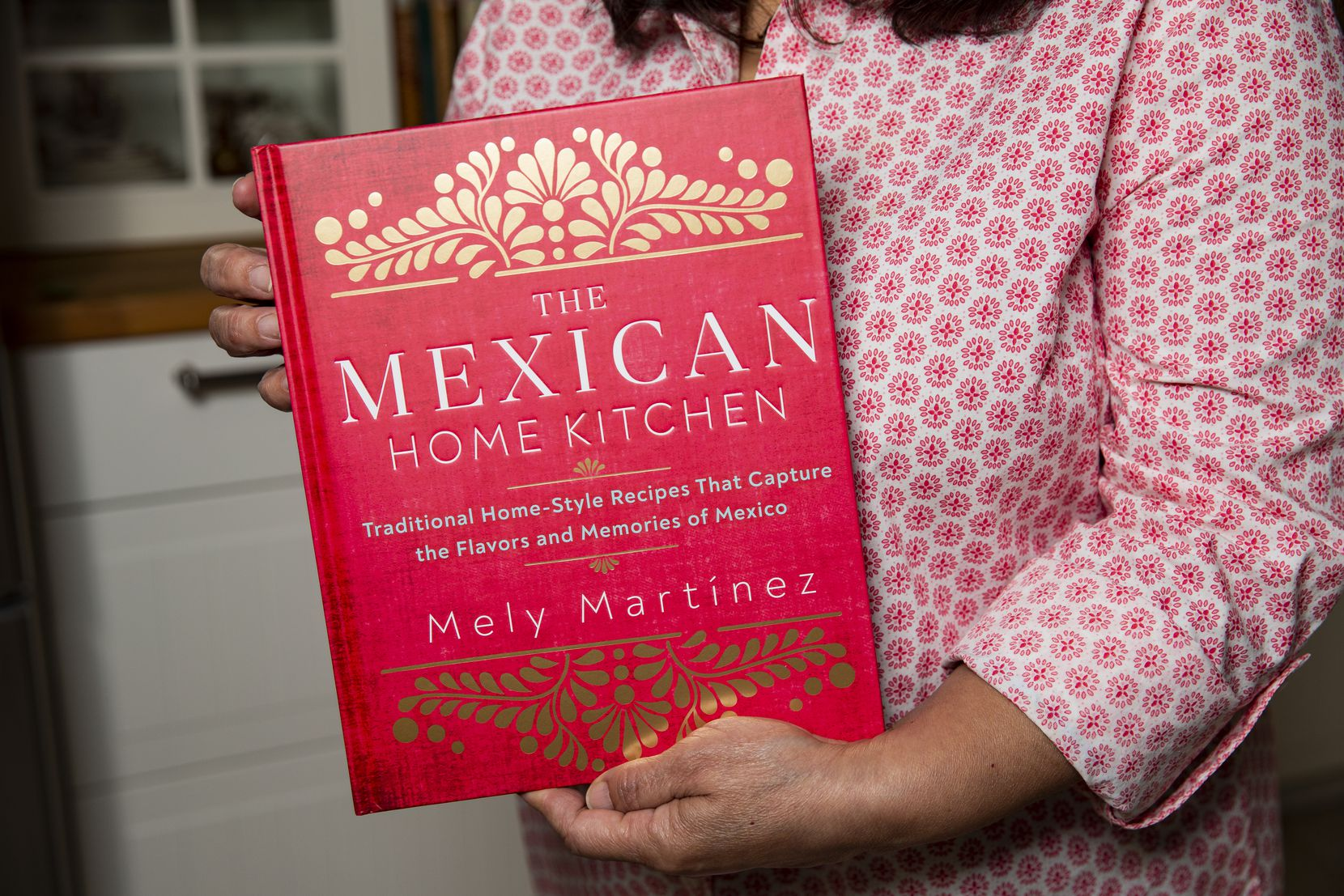 "Local author Mely Martínez holds her recently released cookbook, ""The Mexican Home Kitchen: Traditional Home-Style Recipes That Capture the Flavors and Memories of Mexico."""