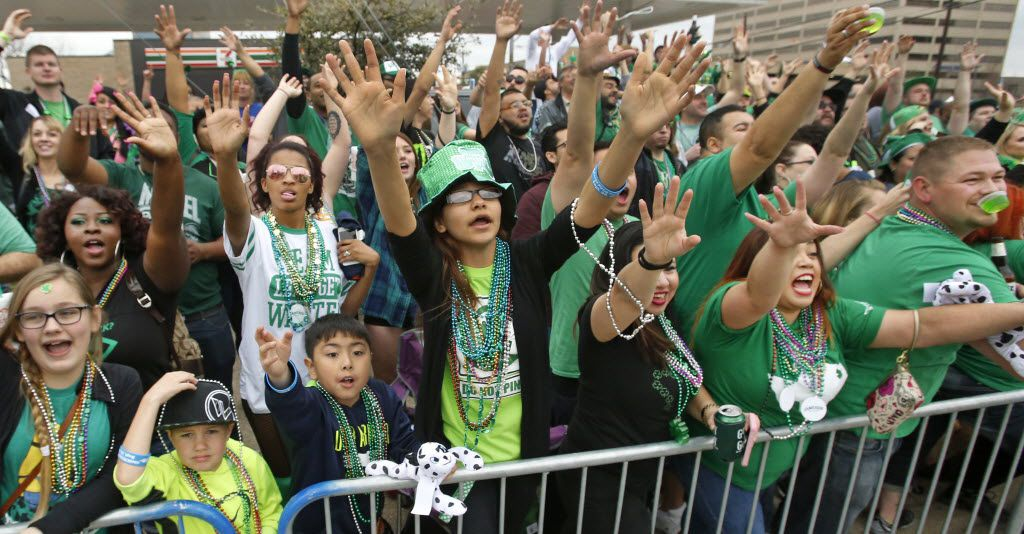 The crowd clamors for beads to be thrown from the passing parade vehicles during the St. Patrick's Day Parade on Greenville Avenue.