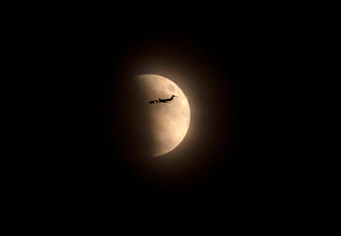 An airplane passes in front of the moon during the lunar eclipse on Sept. 27, 2015, in  Fort Worth.