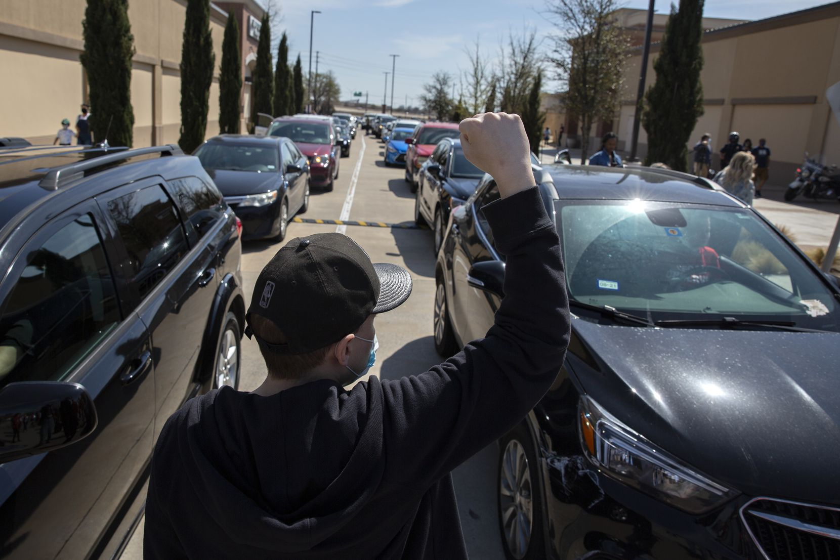 Max Bolen III puts up a fist towards the backed up traffic into the Allen Outlets on Sunday, March 21, 2021 due to a demonstration. Demonstrators called for the arrest of the ÒCollin County SevenÓ, the seven Collin County Jail employees who were placed on leave after Marvin Scott IIIÕs death. (Shelby Tauber/Special Contributor)