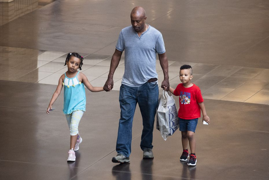 A man walks with his children after shopping at Dillard's inside NorthPark Center in Dallas.