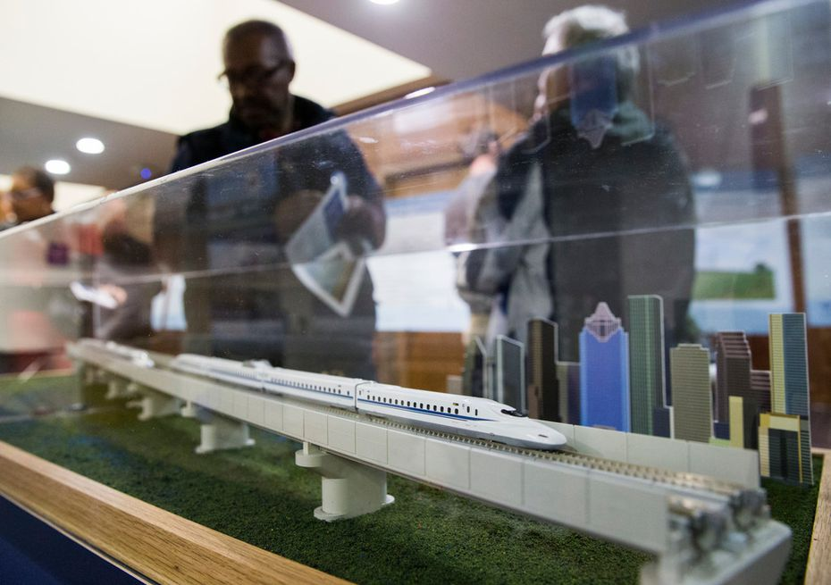 People walk past a model of a $15 billion Dallas to Houston high-speed rail line during an open house for residents to view plans and talk to company and corporate officials at Wilmer-Hutchins High School in Dallas. Texas Central is the builder for the project.