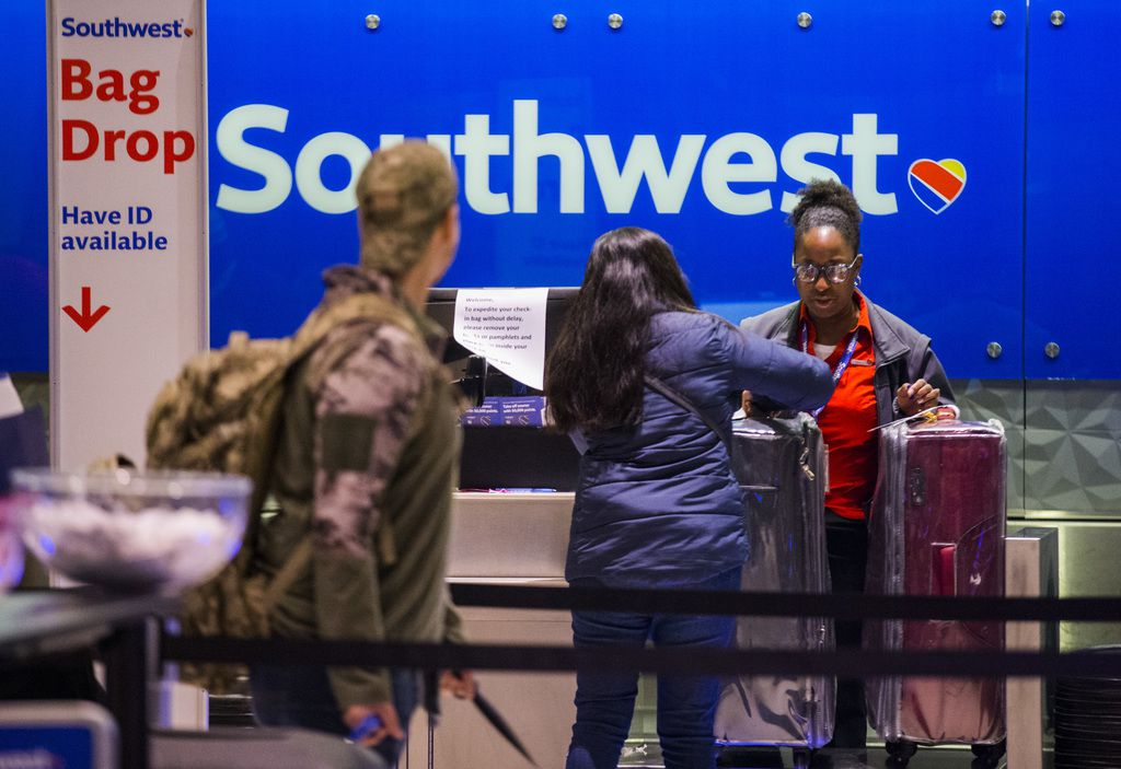 Southwest Airlines employees check in passengers at Love Field Airport on Thursday, January 3, 2019 in Dallas.