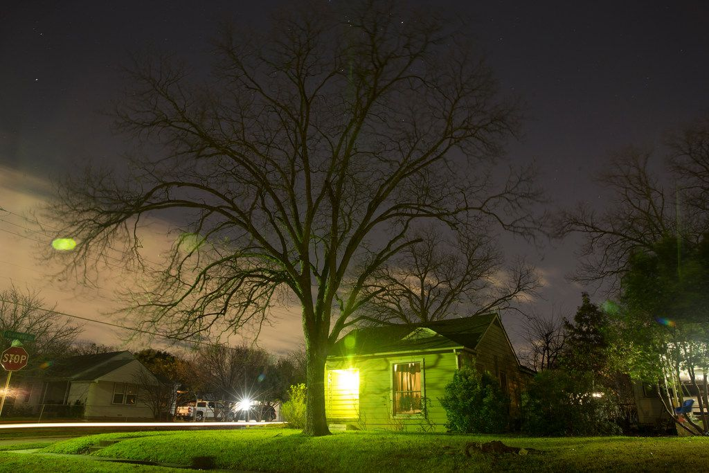 Street lights, a vehicle and a porch light illuminates Ivandell Avenue in the West Oak Cliff neighborhood in Dallas on Friday, December 14, 2018. (Daniel Carde/The Dallas Morning News)