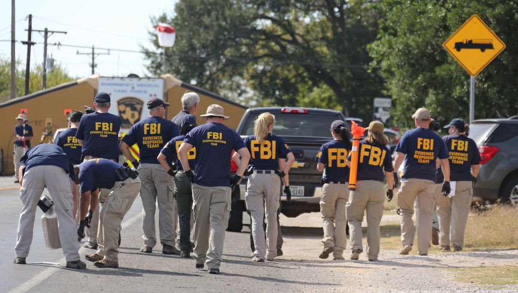 A team of FBI personnel walks the adjacent property looking for evidence at the First Baptist Church of Sutherland Springs in Sutherland Springs, Texas. At least 26 people died Sunday after a gunman opened fire at a Baptist church in the small town southeast of San Antonio. Photographed on Monday, November 6, 2017. (Louis DeLuca/The Dallas Morning News)