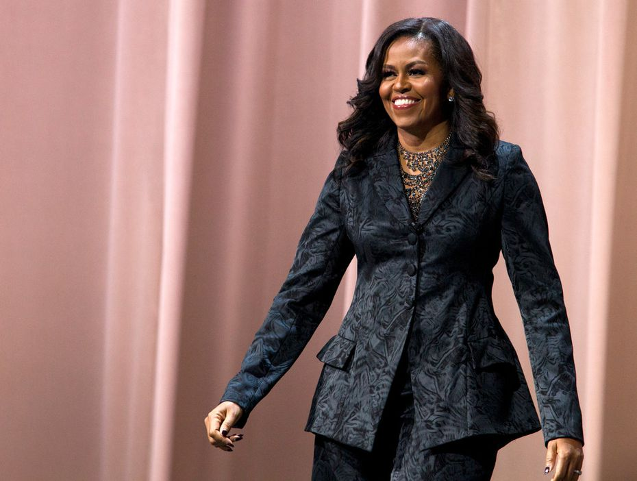 "Former first lady Michelle Obama walks on stage during a stop on her book tour for ""Becoming,"" in Washington."