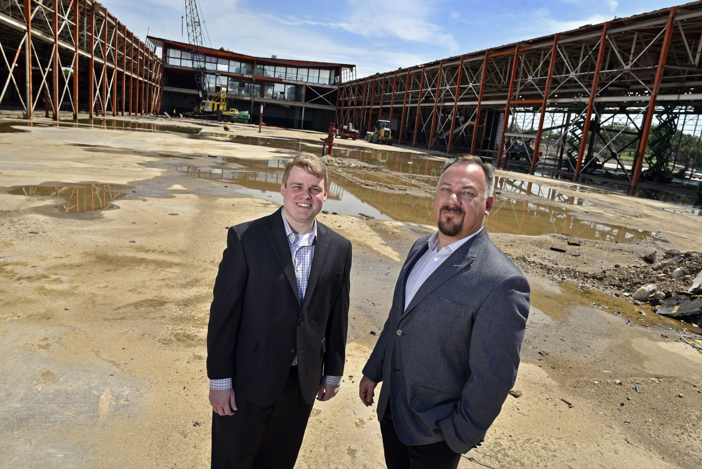 Casey Park (left), director of investments at TAC Investments, and Tad Perryman, VP of marketing at The Arnold Cos., outside of the old Braniff base at Dallas Love Field. The landmark Braniff buildings are being turned into a business center.