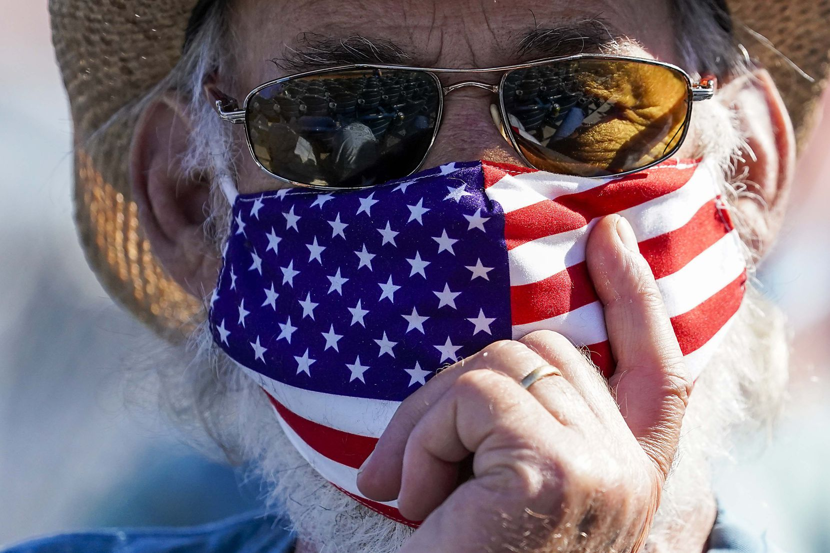 A fan wears an American flag face covering during the fourth inning of a spring training game between the Texas Rangers and the Seattle Mariners at Peoria Sports Complex on Wednesday, March 10, 2021, in Peoria, Ariz.