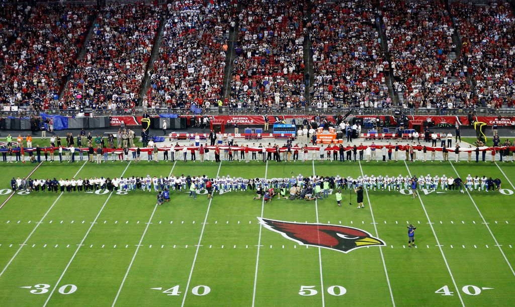 Dallas Cowboys players and staff including owner Jerry Jones and head coach Jason Garrett all take a knee before the singing of the National Anthem prior to the start of a game against the Arizona Cardinals at University of Phoenix Stadium in Glendale, Arizona on Monday, September 25, 2017. (Vernon Bryant/The Dallas Morning News)
