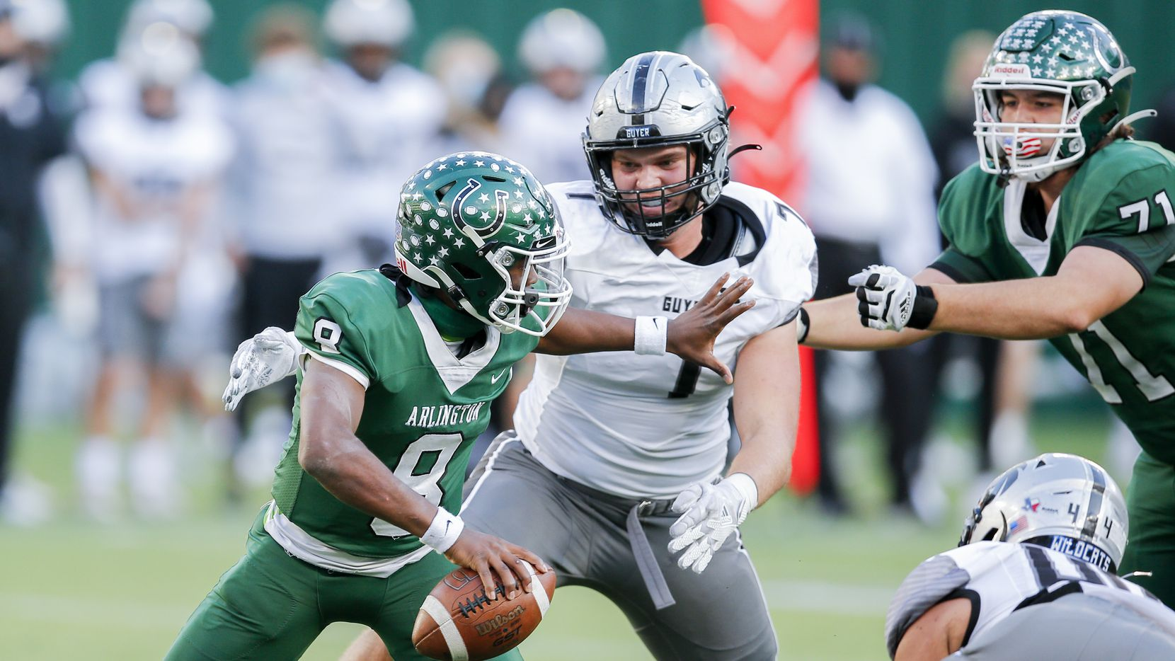 Denton Guyer senior defensive end Cooper Lanz (7) hurries Arlington quarterback Kris Sims (8) during the first half of a high school class 6A Division II area-round playoff game at Globe Life Park in Arlington, Saturday, December 19, 2020.