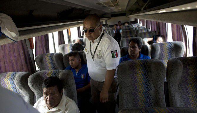 Un agente mexicano de inmigración revisa un autobús en busca de inmigrantes centroamericanos en un retén de Arriaga, Chiapas. (AP/REBECCA BLACKWELL)
