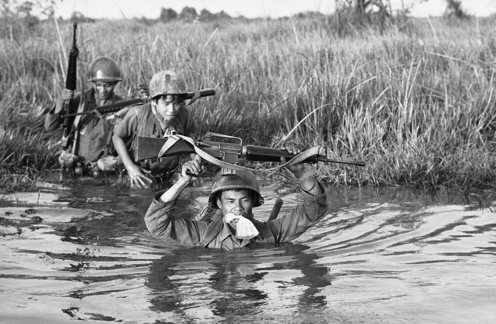 In this March 11, 1972 file photo, a South Vietnamese soldier holds his personal belongings in a plastic bag between his teeth as his unit crosses a muddy Mekong Delta stream in Vietnam near the Cambodian border. His unit was charged with stemming Communist infiltration from Cambodia into South Vietnam in the heavily populated Mekong Delta area.