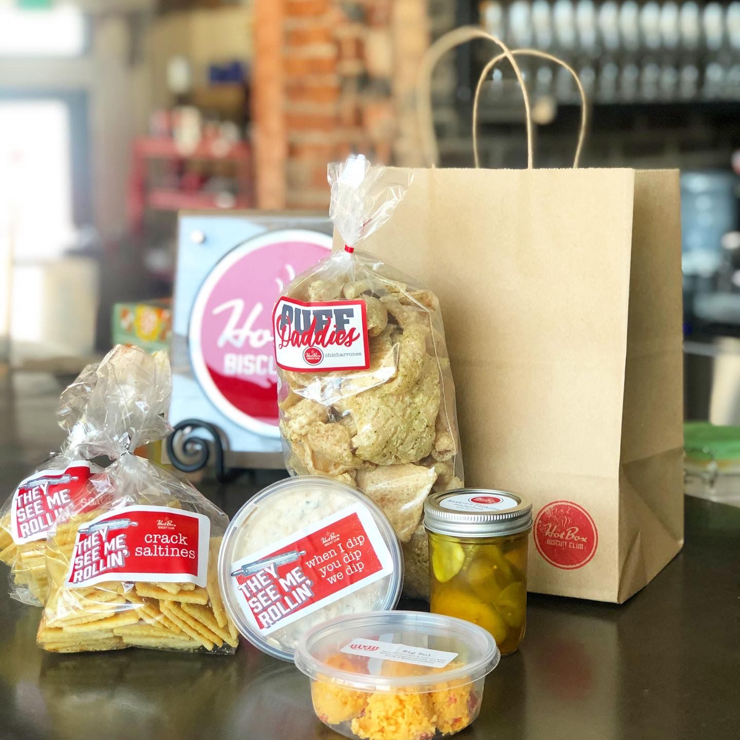Hot Box Biscuit Club is selling snack packages with chips and dip.