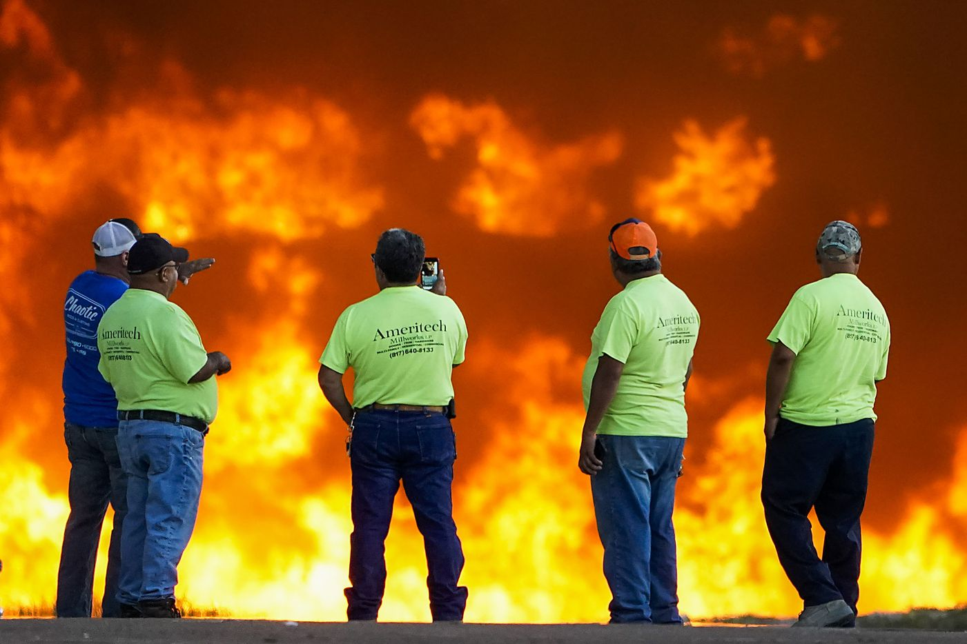 Employees at Ameritech Millworks watch a wall of flames as fire crews battle a massive blaze in an industrial area of Grand Prairie just before sunrise on Wednesday, Aug. 19, 2020.