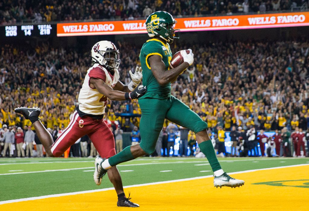 Baylor Bears wide receiver Denzel Mims (5) runs to the end zone for a touchdown ahead of Oklahoma Sooners cornerback Jaden Davis (4) during the first quarter of an NCAA football game between Baylor University and Oklahoma University on Saturday, November 16, 2019 at McLane Stadium in Waco, Texas. (Ashley Landis/The Dallas Morning News)