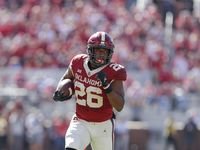 Oklahoma running back Kennedy Brooks (26) runs for a first down against West Virginia during the first half of an NCAA college football game in Norman, Okla., Saturday, Oct. 19, 2019. (AP Photo/Alonzo Adams)