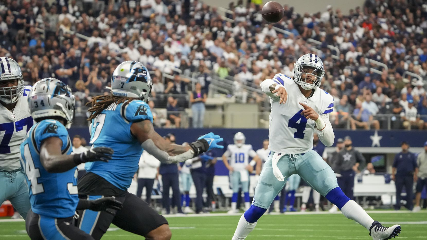 Dallas Cowboys quarterback Dak Prescott (4) makes a throw on the run during the first half of an NFL football game against the Carolina Panthers at AT&T Stadium on Sunday, Oct. 3, 2021, in Arlington.