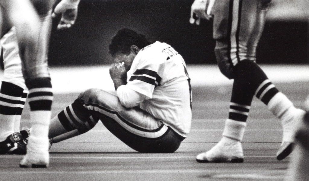 Kicker Luis Zendejas of the Dallas Cowboys sits on the ground and shakes out the cobwebs after getting decked at the beginning of the third quarter of the Dallas Cowboys vs Philadelphia Eagles NFL football game on Nov. 23, 1989. The Thanksgiving Day game came to be known as the Bounty Bowl.