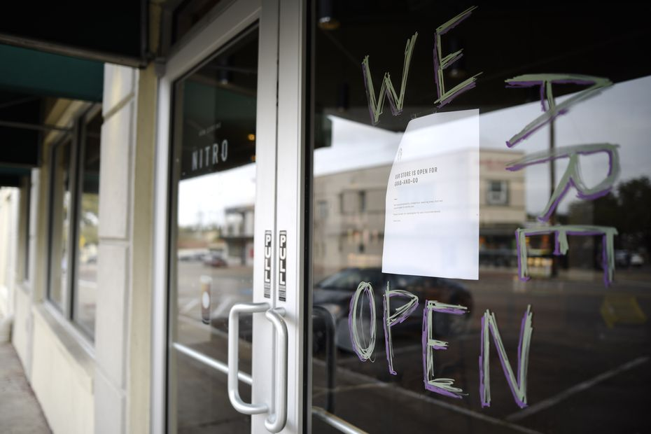 A handwritten sign tells Starbucks customers they are open, despite the fact that the dining room is closed.