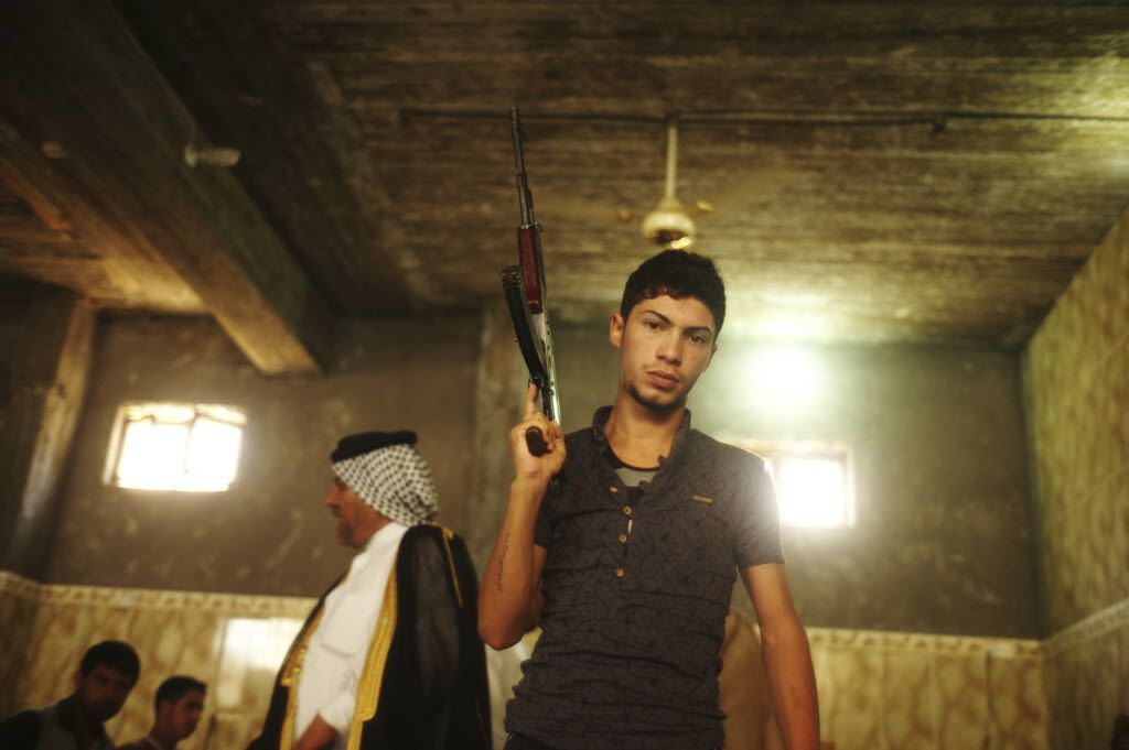 A Shiite volunteer brandishes his weapon at a tribal meeting in Baghdad, June 13, 2014. Grand Ayatollah Ali al-Sistani, Iraq's top Shiite cleric, exhorted all Iraqis to take up arms to defend the state from Sunni militants, as the international community, including Iran, looked for ways to prevent Iraq from descending back into sectarian violence.