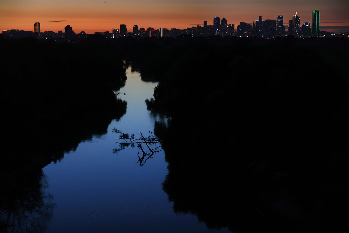 The sun rises over the Trinity River near the Westmoreland bridge early Monday morning, August 30, 2021. The river is known for containing large alligator gar fish. (Tom Fox/The Dallas Morning News)