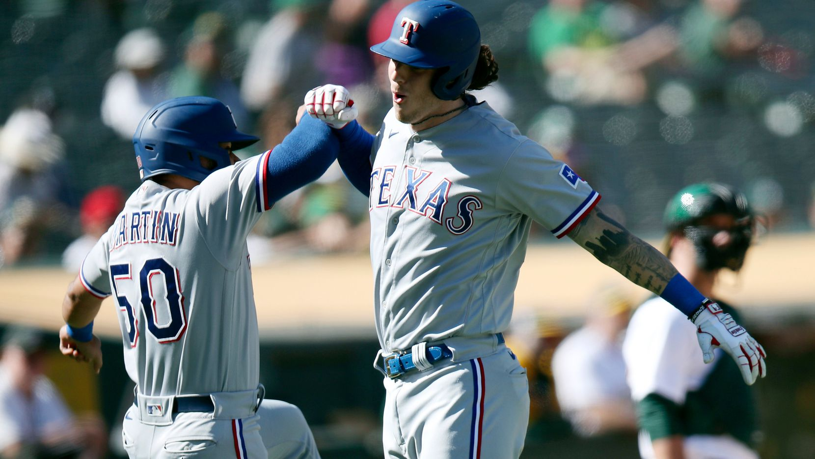 Texas Rangers' Jason Martin (50) congratulates Jonah Heim (28) after he hit a two-run home run in the eighth inning in a baseball game against the Oakland Athletics, Saturday, Sept. 11, 2021, in Oakland. (AP Photo/Scot Tucker)