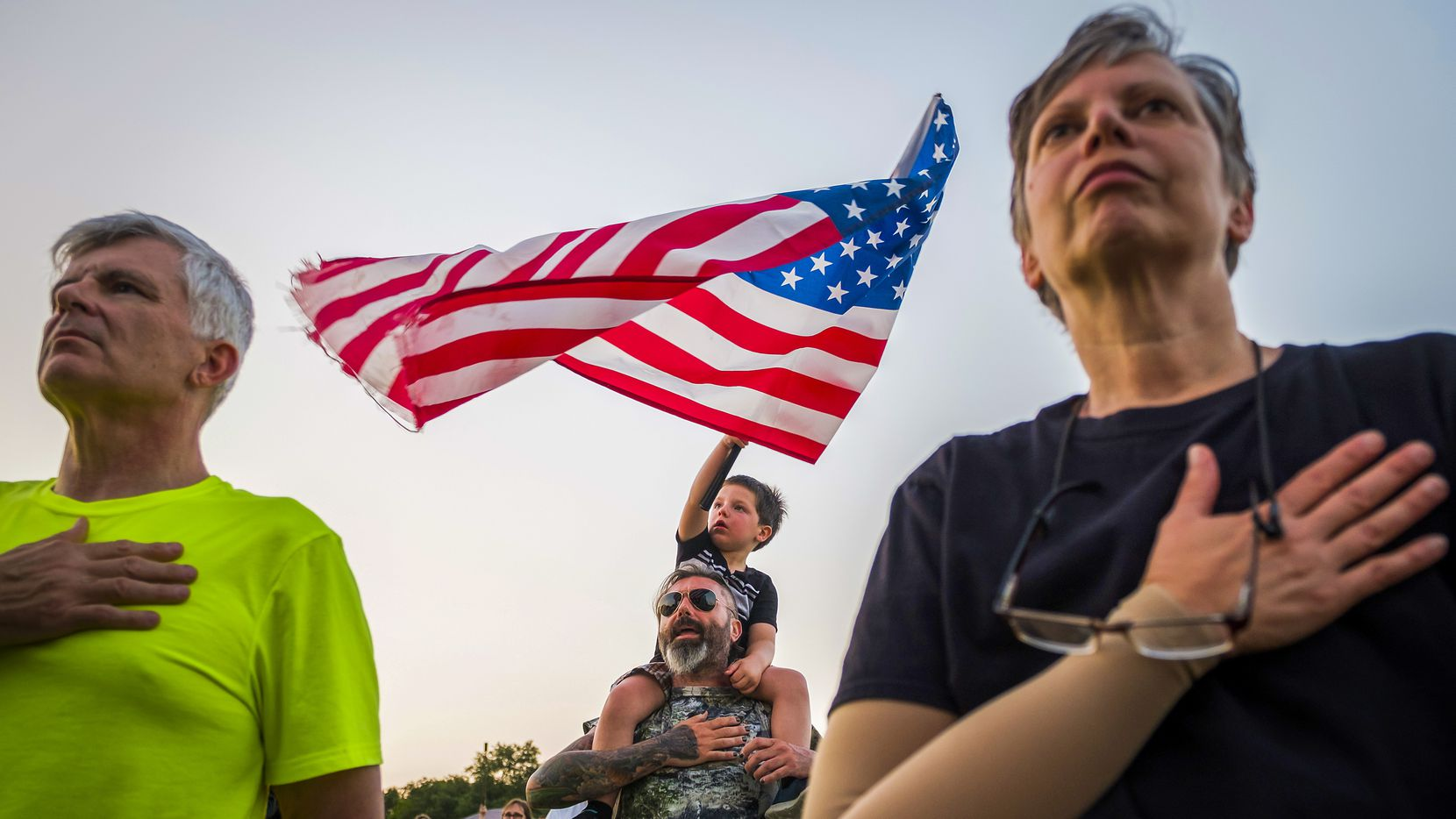 Rian Aganlic waves the American Flag from atop the shoulders of his father Muhamed Aganlic at a previous Dallas Symphony Memorial Day concert at Flag Pole Hill.