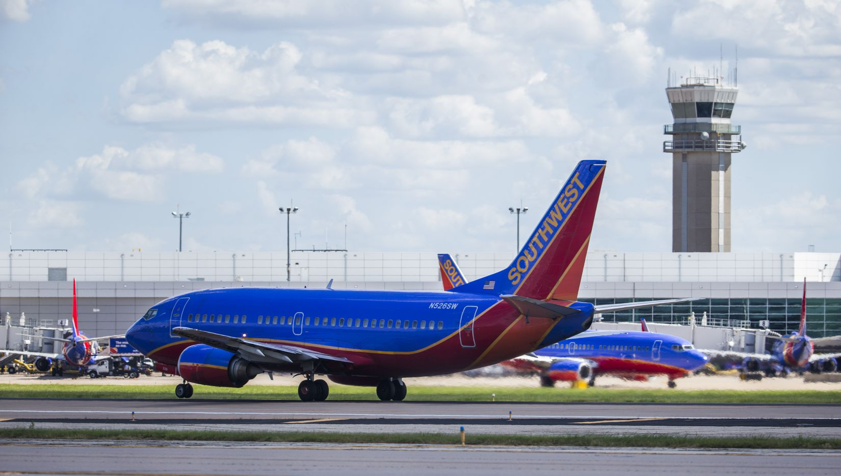 A Southwest Airlines airplane takes off as others remain parked at terminals while computer systems recover from a system-wide crash on Wednesday, July 20, 2016 at Dallas Love Field Airport in Dallas. (Ashley Landis/The Dallas Morning News)