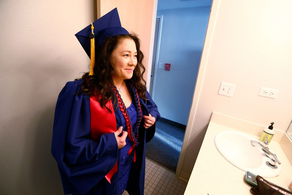Wendy Birdsall looks at herself in the mirror after putting on her cap and gown before graduation from SMU at the SMU Campus Ministry on Friday.