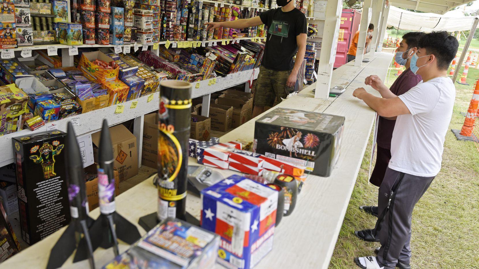 El vendedor Colton Lusk (izq.( ayuda a Cristian López, de 17 años y José Cervera a comprar juegos pirotécnicos en Farmers Fireworks. El dueño de este local afirma que ha vendido más fuegos artificiales que nunca.