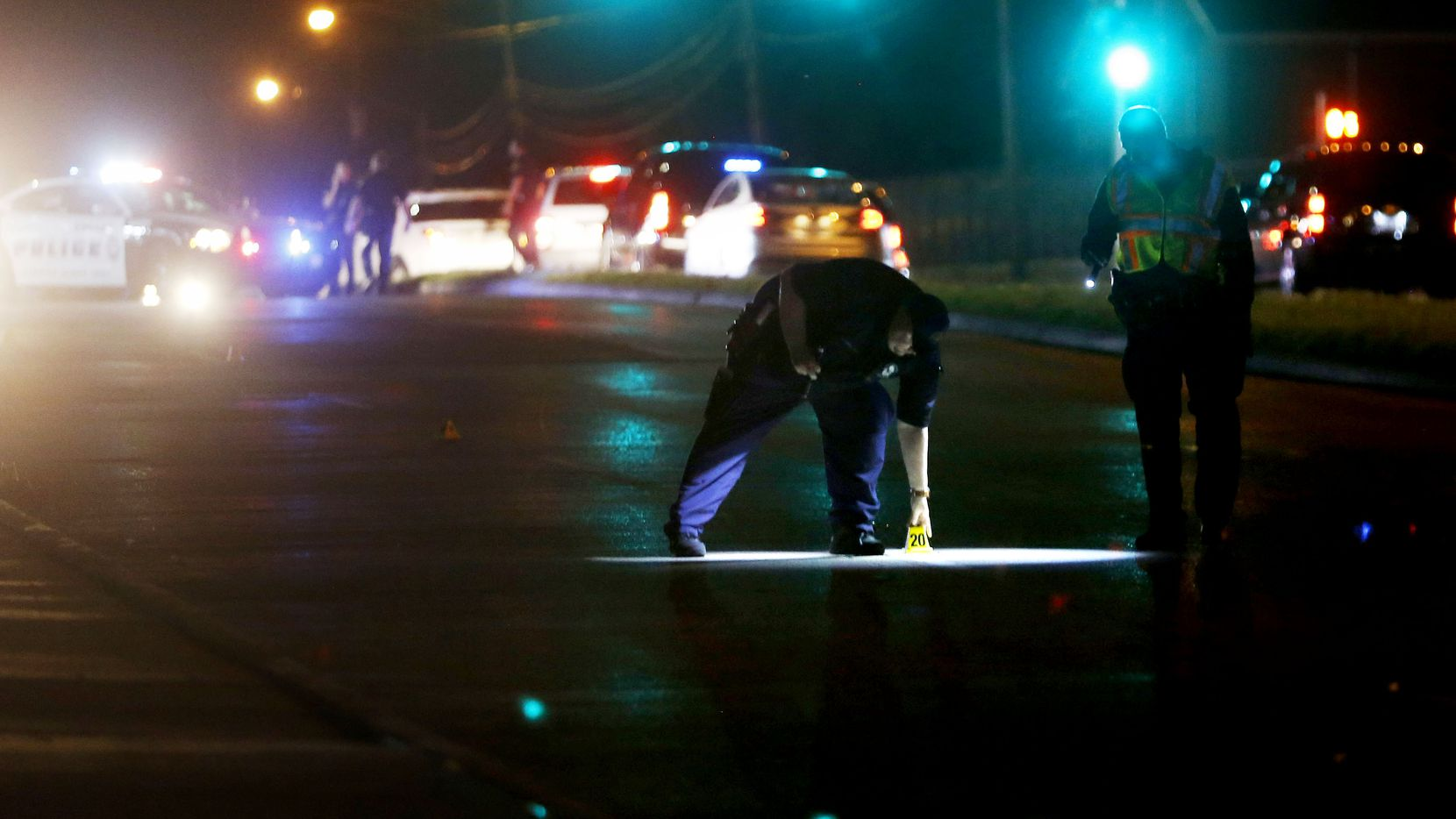 Dallas police mark evidence while investigating the scene of a shooting where a 13-year-old boy died after being caught in crossfire near a Pleasant Grove gas station in the 9400 block of Bruton Avenue in Dallas on June 4, 2019.