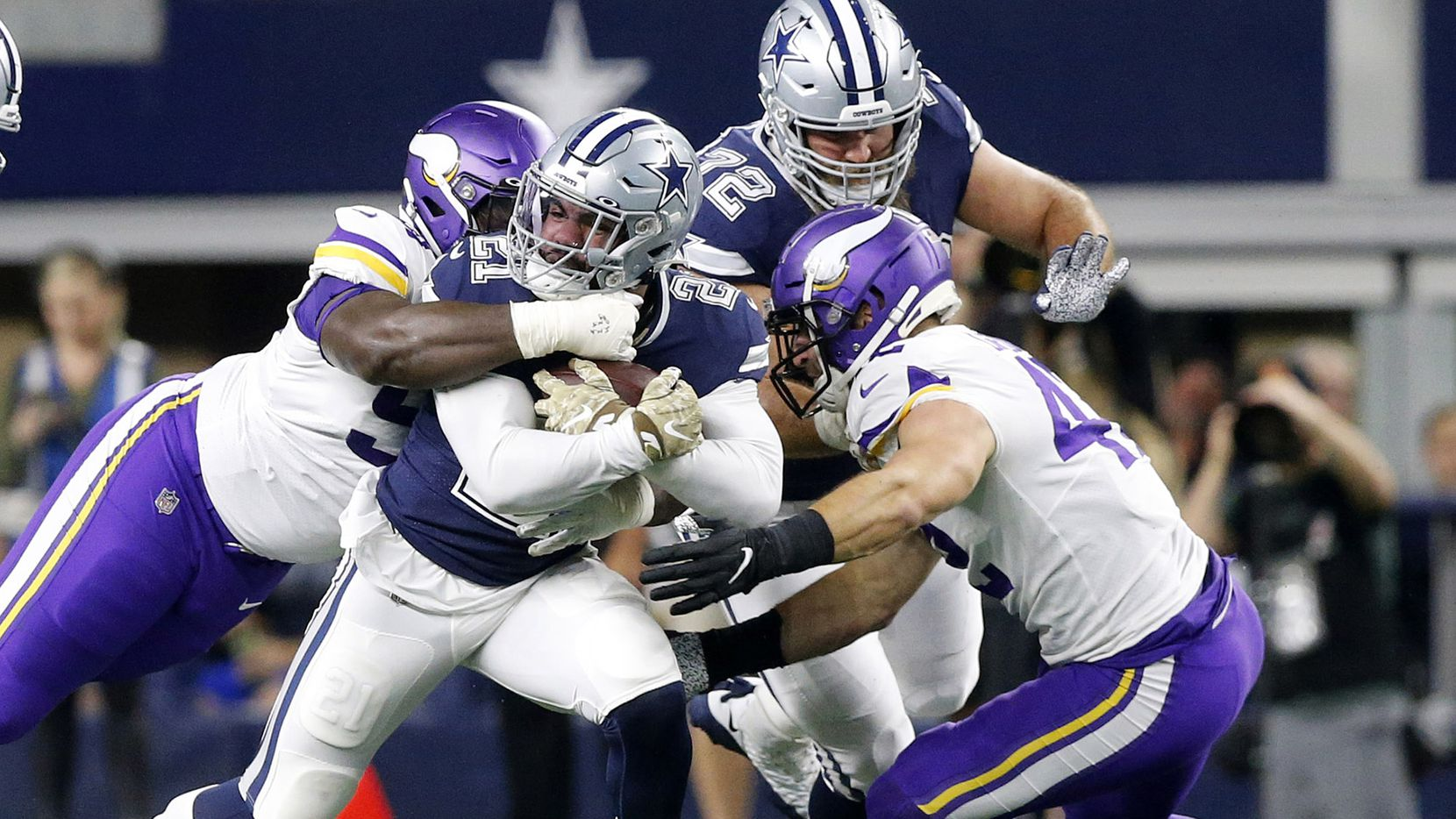 Dallas Cowboys running back Ezekiel Elliott (21) is tackled by the Minnesota Vikings defense during the first quarter on Sunday, Nov. 10, 2019 at AT&T Stadium in Arlington, Texas. (Tom Fox/The Dallas Morning News/TNS)