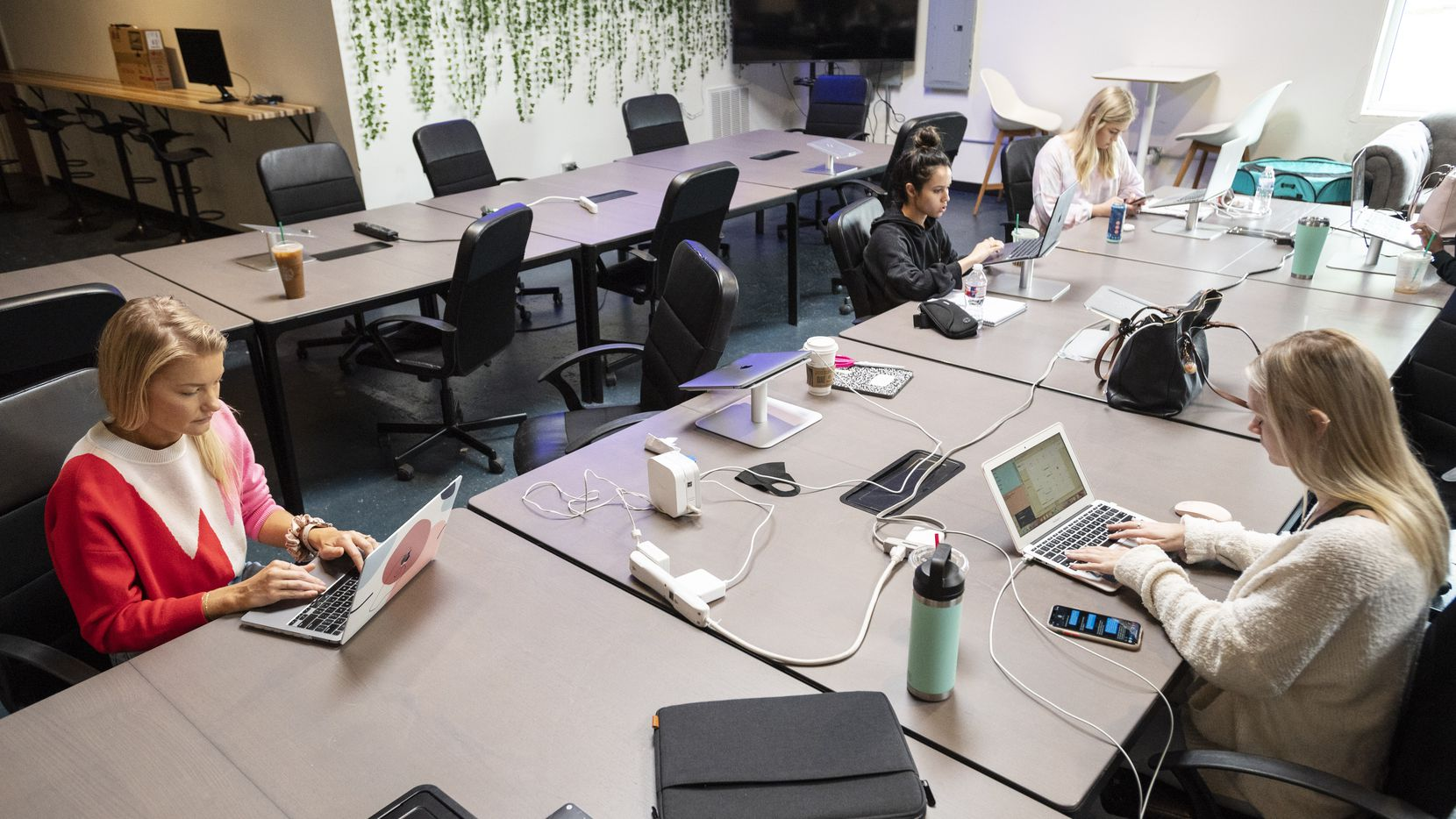 Angela Hagen (far left), director of sales, and apartment locator Ilsa Hargrove (right) work at a group table inside Smart City Apartments' headquarters in Dallas.