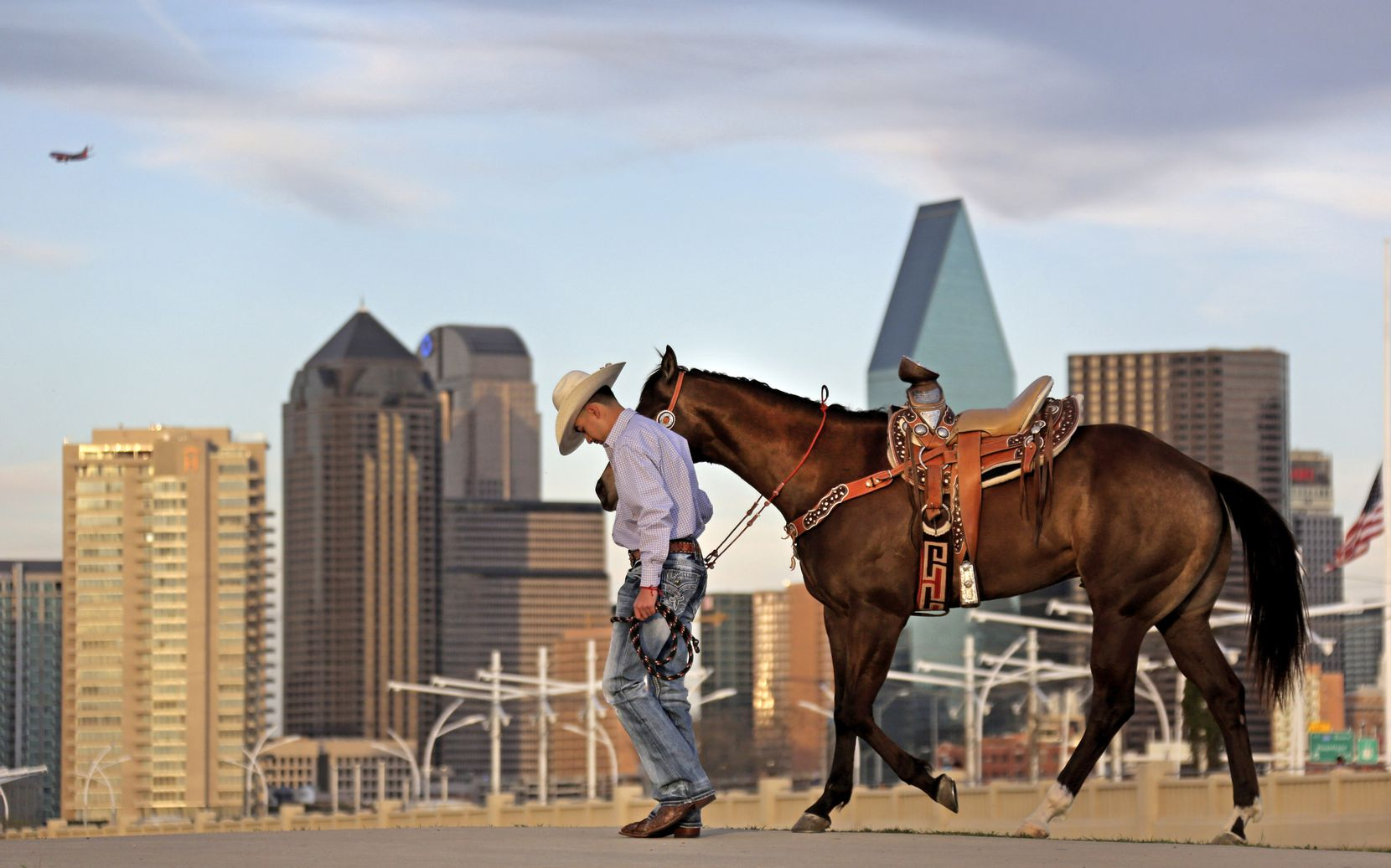 Andrew Salas,who was having his senior portraits taken, walks with his horse on the Trinity River levee in West Dallas, with the downtown Dallas skyline in the background, photographed on Friday, March 16, 2018.
