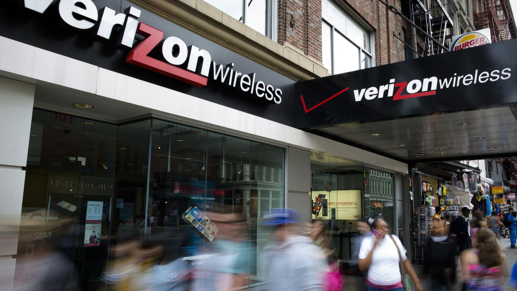 In this file photo, pedestrians pass a Verizon Wireless store on Canal Street in New York.