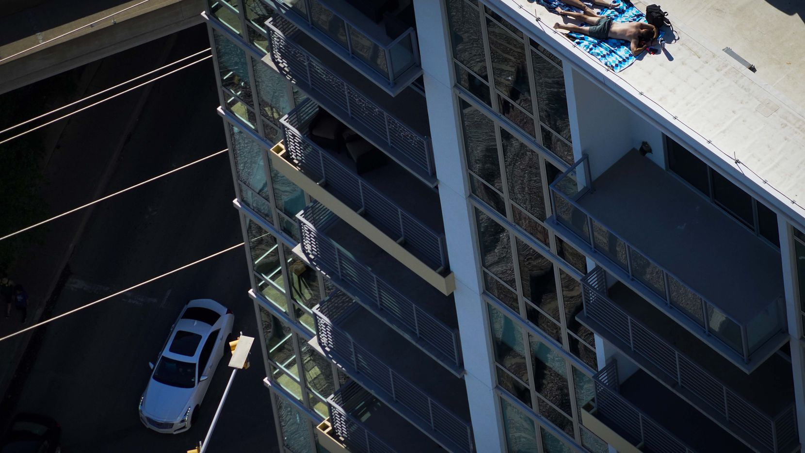 Aerial view of a couple sunbathing on the roof of the The Katy in Victory Park Apartments on Tuesday, March 24, 2020 in Dallas.