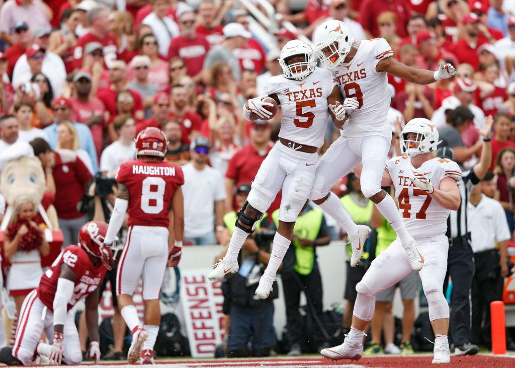 Texas Longhorns running back Tre Watson (5) celebrates with Texas Longhorns wide receiver Collin Johnson (9) after Watson scored a touchdown in a game against the Oklahoma Sooners during the first half of play in a NCAA football game  between Texas Longhorns and the Oklahoma Sooners at the Cotton Bowl in Dallas on Sunday, October 6, 2018. (Vernon Bryant/The Dallas Morning News)