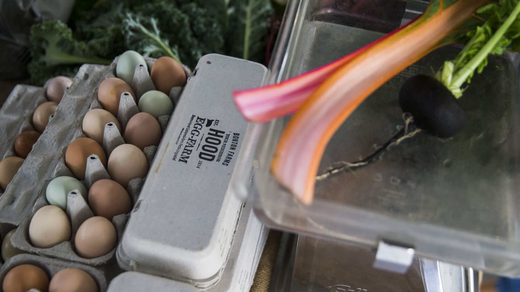 Fresh eggs, along with chard and radishes from Bonton Farms is on sale at the Dallas Farmers Market on Saturday, March 14, 2020.