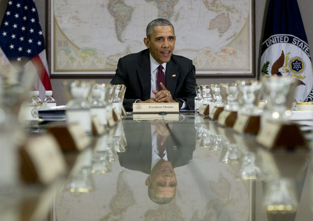 President Barack Obama is reflected in the conference table before a meeting of his National Security Council (NSC) at the State Department in Washington, Thursday, Feb. 25, 2016. The meeting is to focus on the global campaign to degrade and destroy ISIL as well as Syria and other regional issues. (AP Photo/Carolyn Kaster)