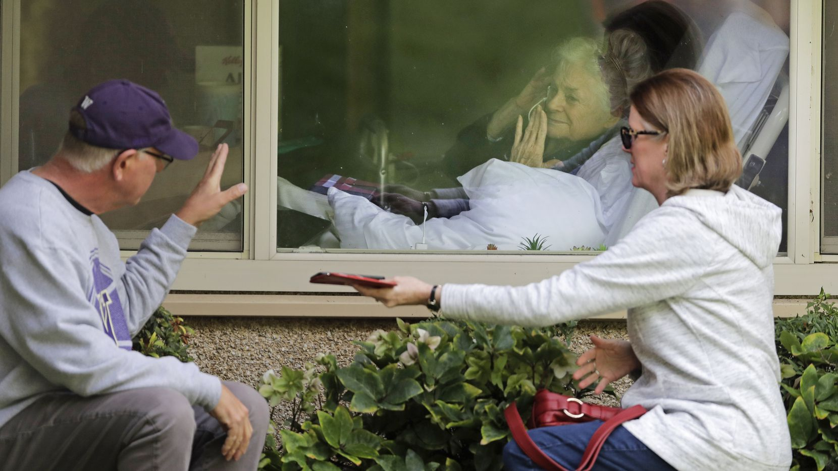 Judie Shape, center, who has tested positive for the coronavirus, blows a kiss to her son-in-law, Michael Spencer, left, as Shape's daughter, Lori Spencer, right, looks on, Wednesday, March 11, 2020, as they visit on the phone and look at each other through a window at the Life Care Center in Kirkland, Wash., near Seattle.
